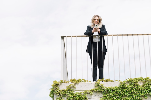 Femme affaires, utilisation, smartphone, balcon Photo gratuit