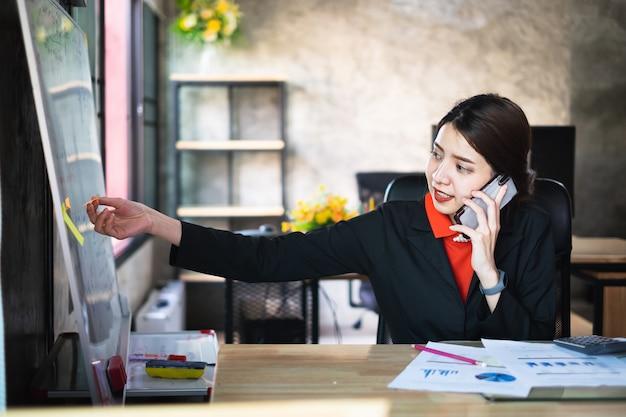 Femme d'affaires vérifiant l'horaire sur le poster et en discutant avec le client par téléphone. Photo Premium