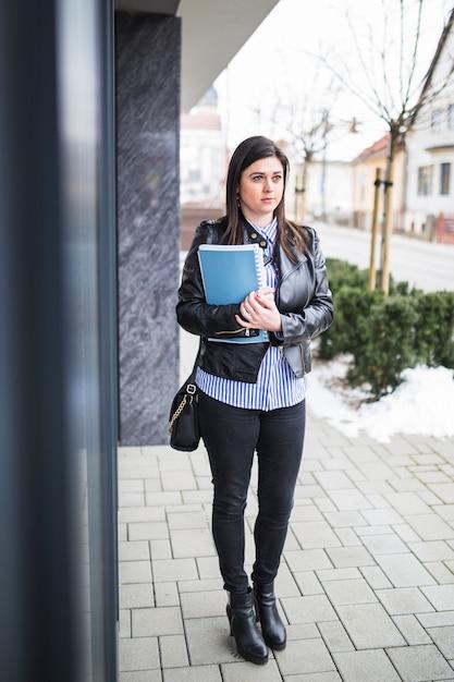 Femme d'affaires, vêtu d'une veste noire avec des livres, debout sur le trottoir Photo gratuit