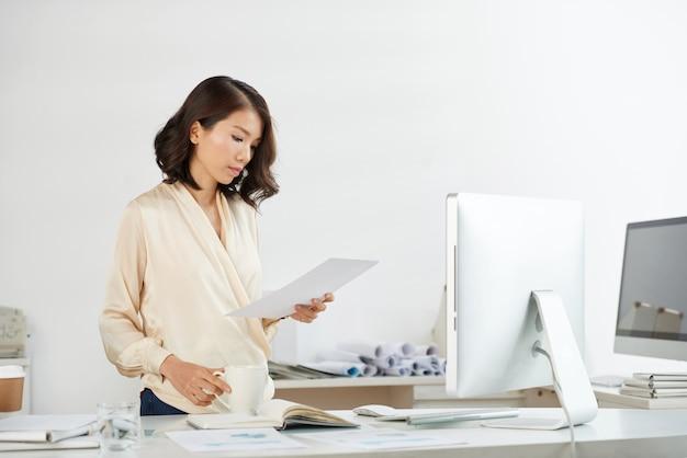 Femme d'affaires vietnamienne vérifiant le document Photo gratuit
