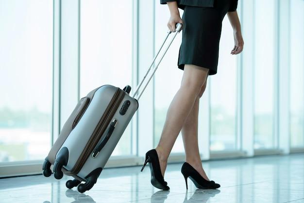 Femme d'affaires voyageant avec chariot. Photo Premium