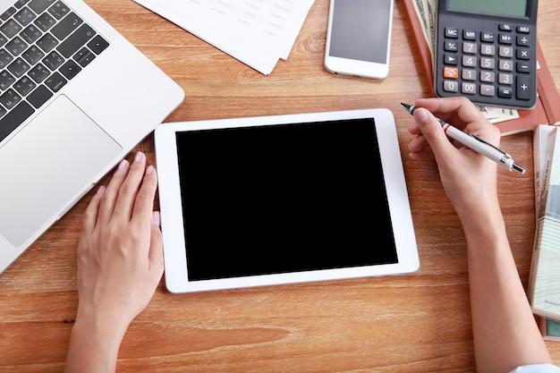 Femme d'affaires vue de dessus utiliser tablette maquette ordinateur portable et papeterie de bureau sur une table en bois Photo Premium