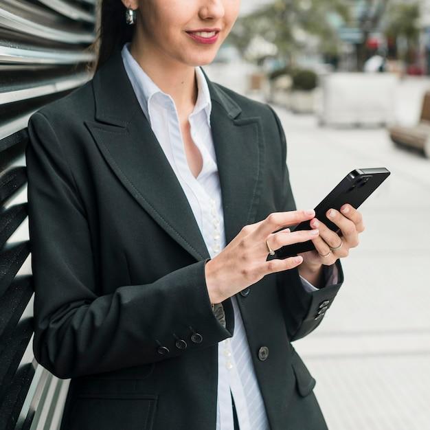 Femme D'affaires Vue De Face Vérifiant Son Smartphone Photo gratuit