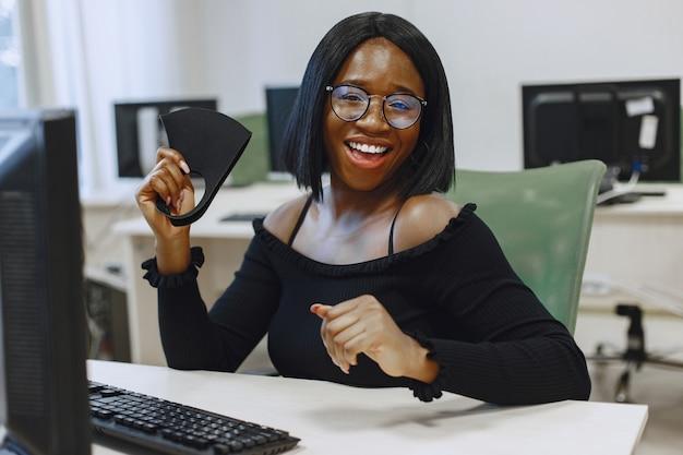 Femme Africaine Assise En Classe D'informatique. Dame à Lunettes Sourit à La Caméra. étudiante Assise à L'ordinateur. Photo gratuit