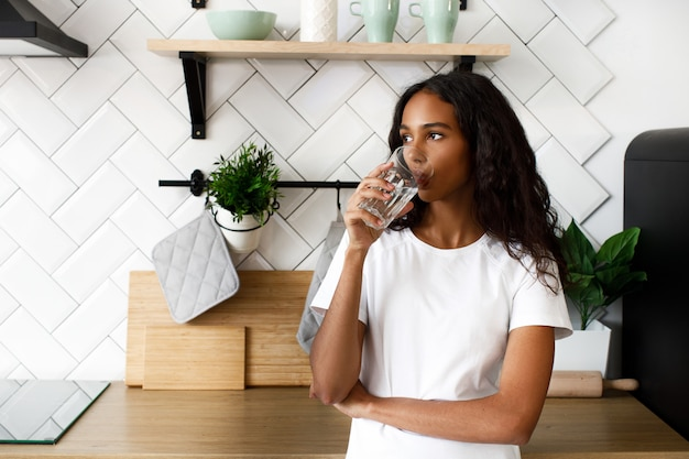 Femme Africaine Se Dresse Sur La Cuisine Et Boit De L'eau Photo gratuit