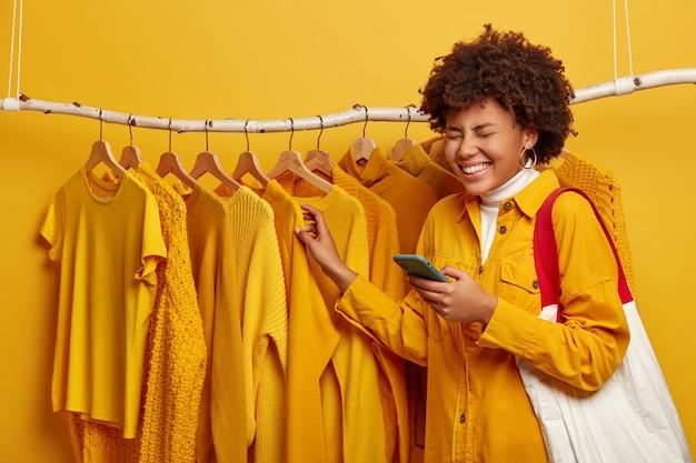 Femme Africaine Vêtue D'une Veste Jaune élégante, Porte Un Sac à Provisions, Utilise Un Téléphone Mobile Pour La Communication En Ligne, Pose Près De Rail De Vêtements Sur Fond Jaune Photo gratuit