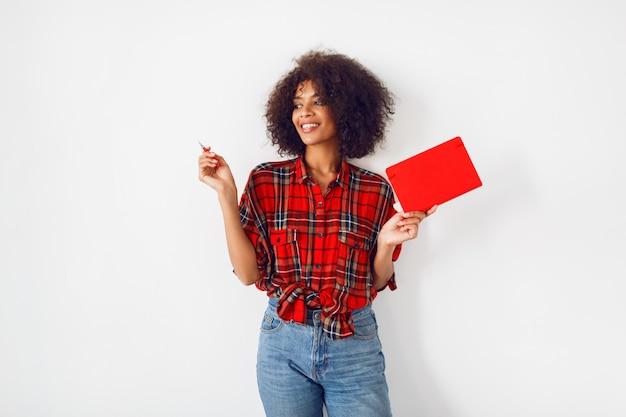 Femme Africaine Avec Visage Surprise Tenant Le Cahier Et Pointant Vers Le Haut. émotions Drôles. Fond Blanc. Photo gratuit