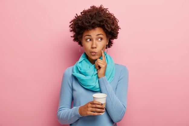 Femme Afro-américaine Bouclée Garde L'index Sur La Joue, Regarde Pensivement De Côté, Envisage Quelque Chose Avec Une Boisson Chaude, Tient Une Tasse En Papier, Porte Un Pull Bleu, A Une Pause-café Isolée Sur Un Mur Rose Photo gratuit