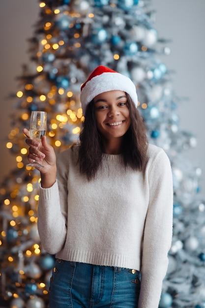 Femme Afro-américaine Avec Une Coupe De Champagne à La Maison. Célébration De Noël Photo gratuit