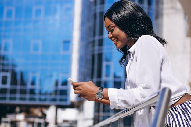 Femme afro-américaine à l'extérieur par le gratte-ciel avec téléphone Photo gratuit