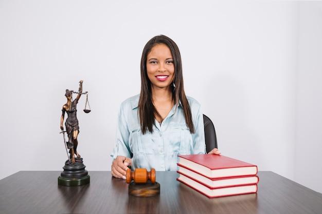 Femme afro-américaine joyeuse à table avec marteau, livres et statue Photo gratuit