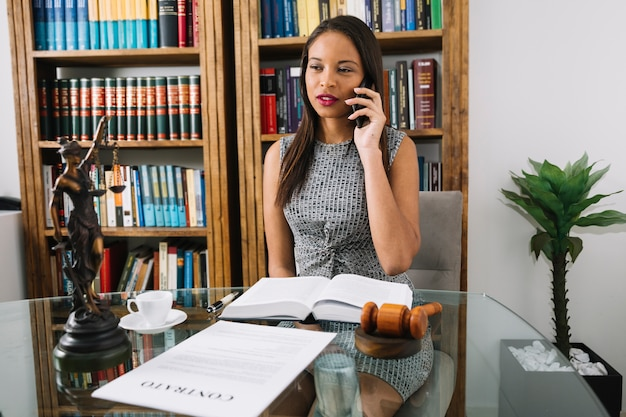 Femme afro-américaine parlant sur smartphone à la table de bureau Photo gratuit