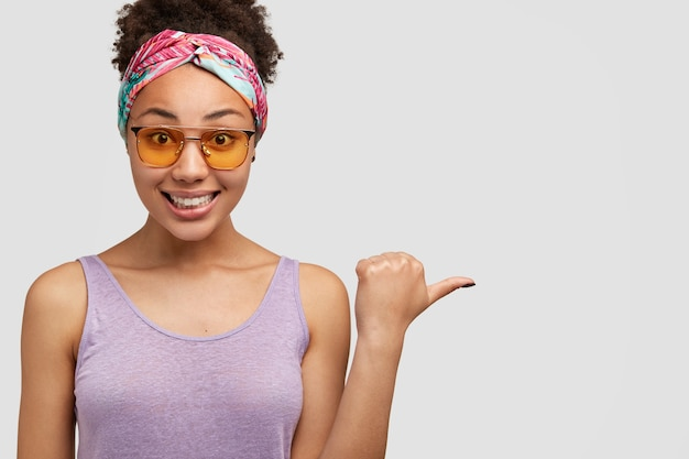 Femme Afro-américaine Positive Avec Un Sourire Doux Pointant Sur Copyspace Photo gratuit