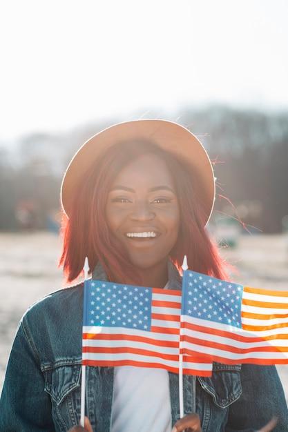 Femme afro-américaine souriante avec des drapeaux américains Photo gratuit