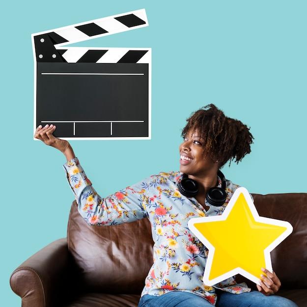 Femme afro-américaine tenant une icône de clapet Photo gratuit