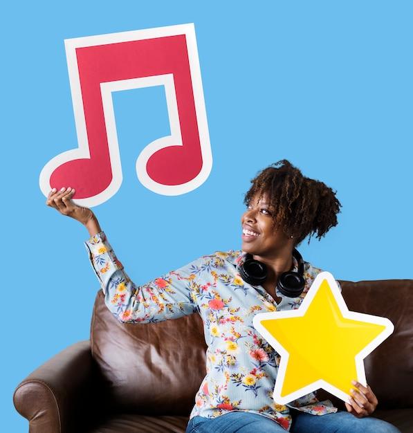 Femme afro-américaine tenant une note de musique Photo gratuit