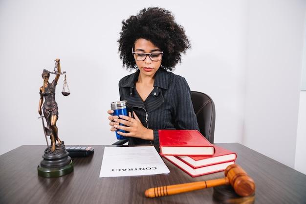 Femme afro-américaine avec thermos à table près de calculatrice, livres, document et statue Photo gratuit
