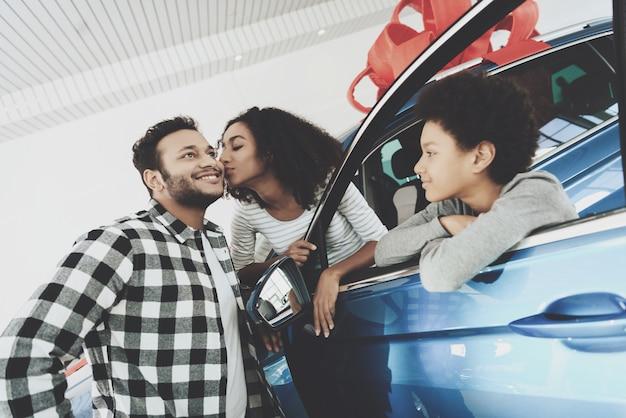 Une femme afro donne un baiser à son mari pour une voiture-cadeau. Photo Premium