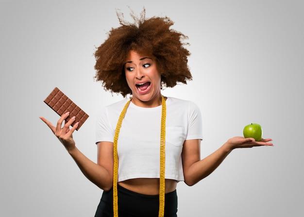 Femme afro jeune fitness choisissant entre manger sainement ou au chocolat Photo Premium