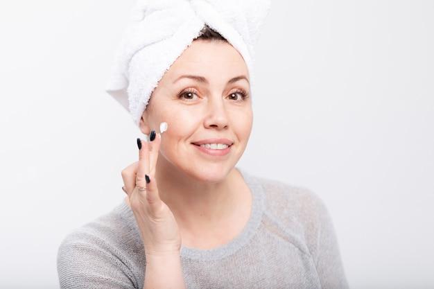 Femme D'âge Moyen Appliquant Une Crème Anti-âge Avant Miroir Photo Premium