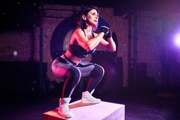 Femme d'âge moyen fit attrayant faire la boîte à sauter à un style croisé. athlète féminine effectue des sauts au gymnase Photo Premium