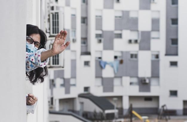 Femme D'âge Moyen Avec Un Masque Facial Disant Au Revoir à Un Parent De Sa Fenêtre. Isolé à La Maison. Contexte Des Bâtiments Résidentiels. Photo Premium