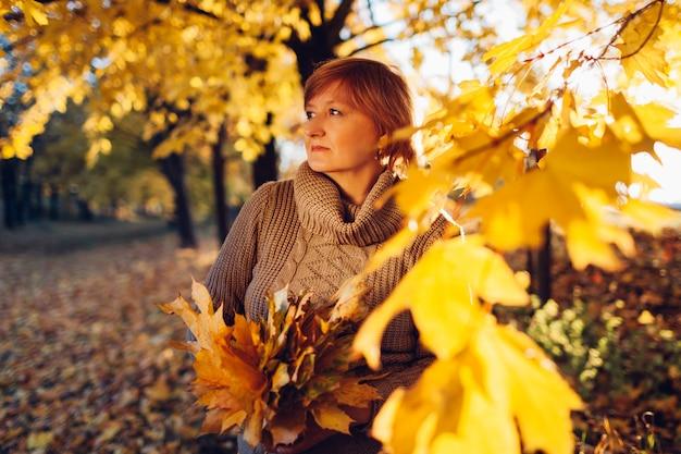Femme D'âge Moyen Qui Marche Avec Bouquet D'érable Feuilles Dans La Forêt D'automne. Paysage D'automne Photo Premium