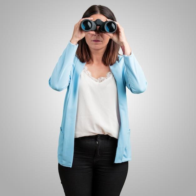 Femme d'âge moyen surpris et surpris, regardant avec des jumelles au loin Photo Premium