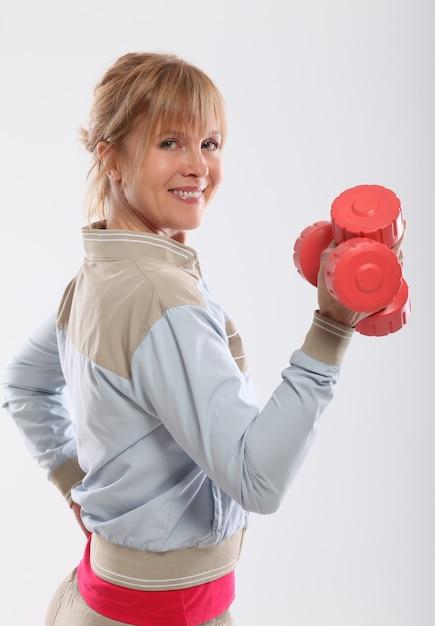 Femme d'âge moyen, travailler avec des haltères rouges Photo gratuit