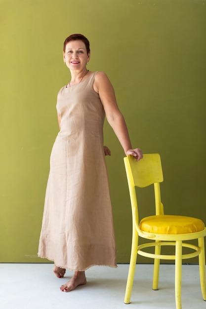 Femme d'âge mûr avec une chaise jaune Photo gratuit