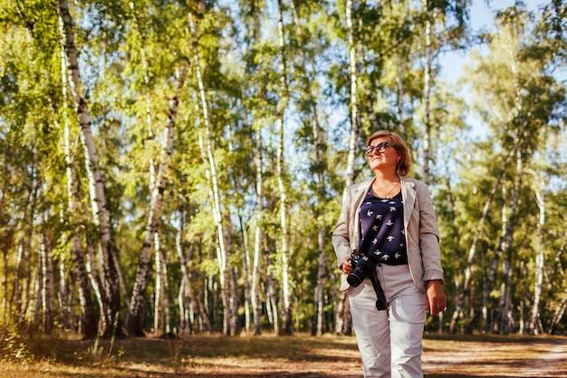 Femme D'âge Mûr Prenant Des Photos à L'aide De La Caméra Dans La Forêt D'automne. Senior Femme Marchant Photo Premium