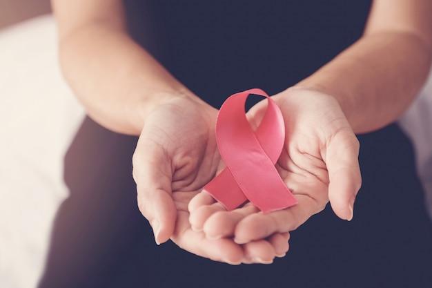 Femme d'âge mûr tenant un ruban rose, sensibilisation au cancer du sein, octobre rose Photo Premium