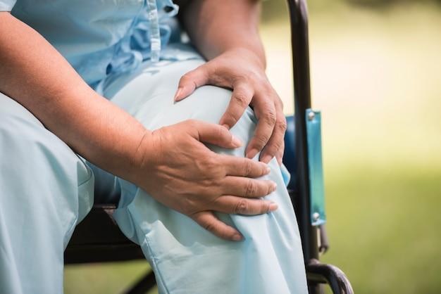 Femme âgée assise sur un fauteuil roulant avec une douleur au genou Photo gratuit