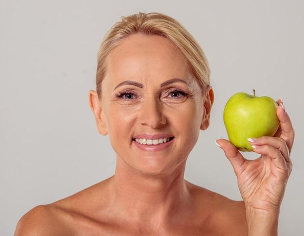 Femme âgée aux épaules nues tenant une pomme. Photo Premium