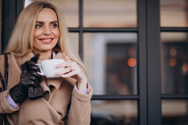 Femme âgée, Boire Du Café à L'extérieur Du Café Photo gratuit