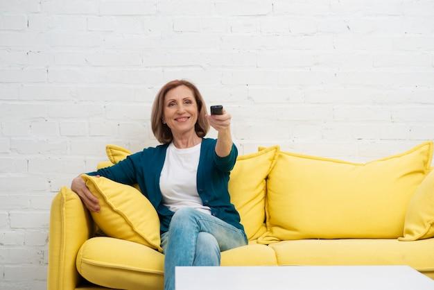 Une femme âgée change de chaîne de télévision Photo gratuit