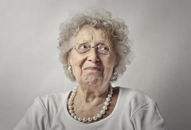 Femme âgée Contre Un Mur Blanc Avec Un Regard Inquiet Sur Son Visage Photo gratuit