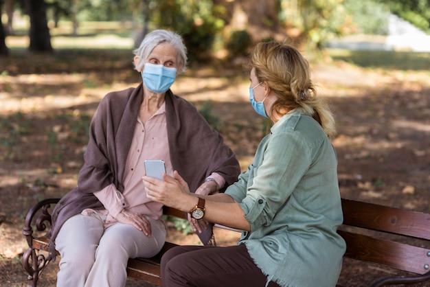 Femme âgée Conversant Avec Une Femme Sur Un Banc à L'extérieur Tout En Tenant Un Smartphone Photo gratuit