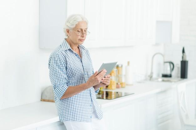 Femme âgée, debout, cuisine, regarder, tablette numérique Photo gratuit