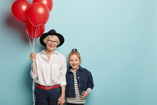Une Femme âgée Joyeuse Et Une Petite-fille Se Tiennent La Main, Ont Une Attitude Positive, Des Expressions Faciales Heureuses, Portent Une Tenue élégante, Assistez à Un événement Festif Consacré à La Journée Des Enfants Deux Générations Photo gratuit