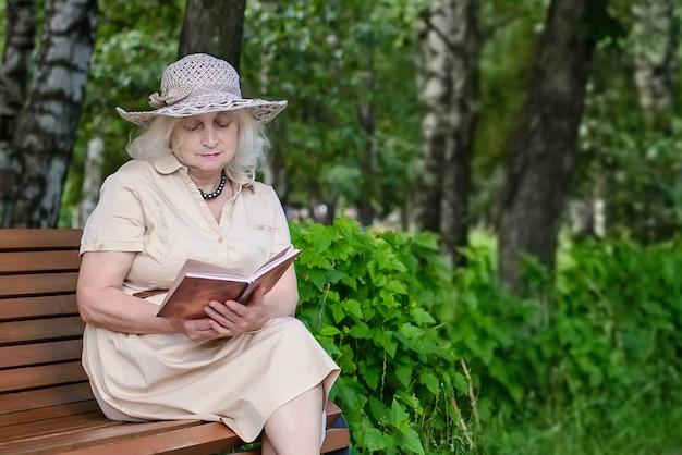 Une Femme âgée Lit Un Livre Dans Le Parc Photo Premium