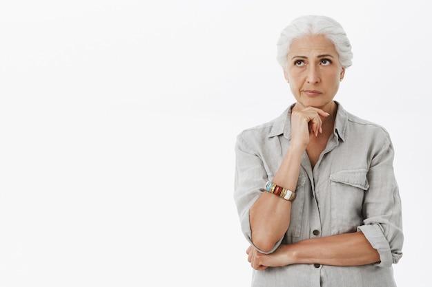 Femme âgée Pensif Troublé Aux Cheveux Gris, à La Réflexion Dans Le Coin Supérieur Gauche Photo gratuit