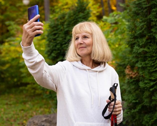 Femme âgée Prenant Un Selfie Lors D'une Randonnée En Plein Air Photo gratuit