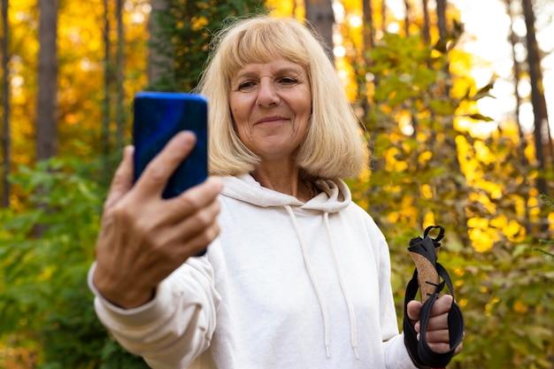 Femme âgée Prenant Un Selfie Lors D'un Trekking Dans La Nature Photo gratuit