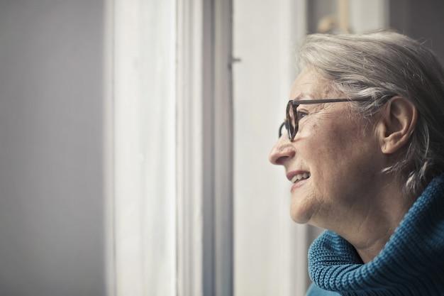 Femme âgée regardant par la fenêtre Photo Premium