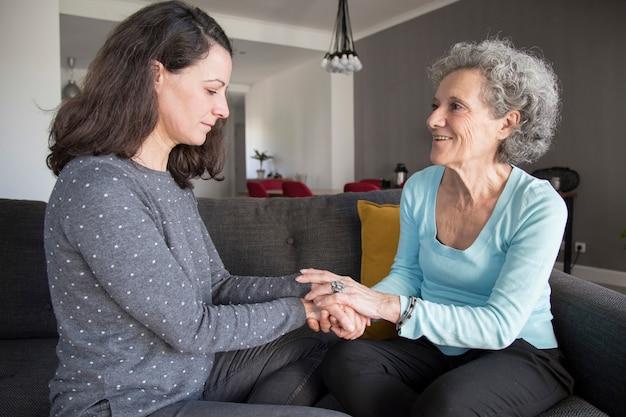 Femme âgée et sa fille discutant et se tenant la main Photo gratuit