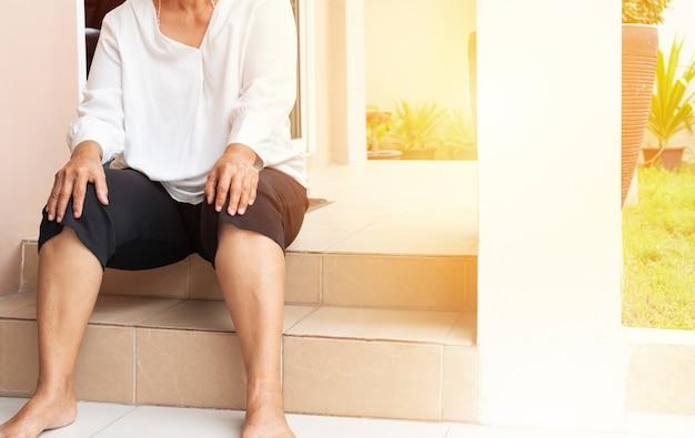 Femme âgée souffrant de douleur au genou à la maison, notion de problème de santé Photo Premium