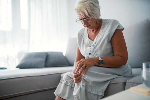 Femme âgée souffrant de douleurs au genou chez elle Photo Premium