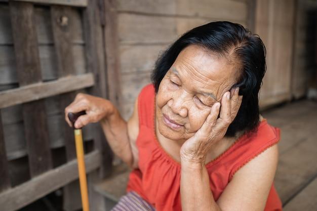Femme âgée Thaïlandaise En Col Rond Sans Manches Avec Maux De Tête Et Visage Stressé Inquiet Dans La Vieille Maison En Bois Photo Premium