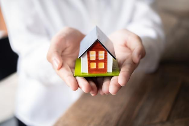 Femme Agent Immobilier Main Tenant Le Modèle De Maison, Concept Immobilier. Photo Premium